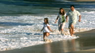 Family runs on beach together, slow motion video