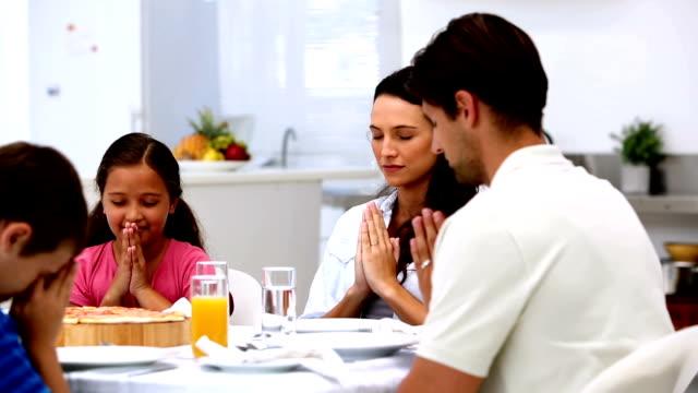 Family saying grace before dinner video