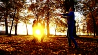 SLO MO Family scattering leaves at dusk video