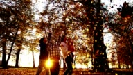 SLO MO Family scattering leaves at sunset video