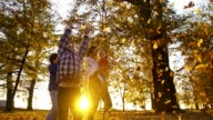 SLO MO Family scattering leaves over themselves video