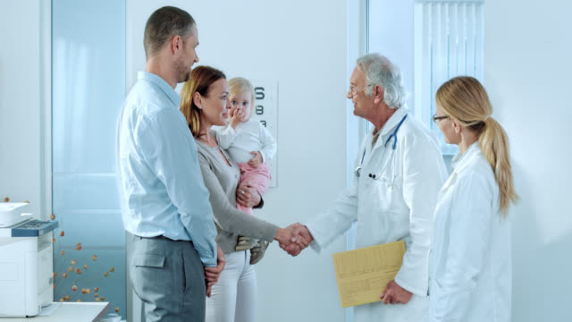Family shaking hands with the staff physician in office video