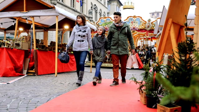 Family shopping in busy and decorated city street in Christmas video