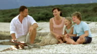 Family singing on island beach by the fire video