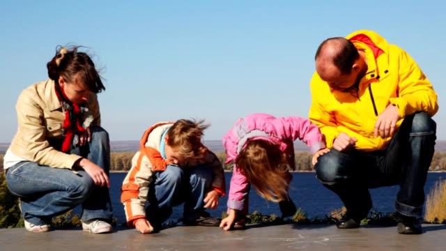 Family sits and draws on asphalt chalk video