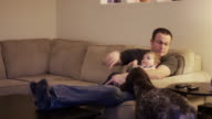 A family sits down on the couch to watch television together video