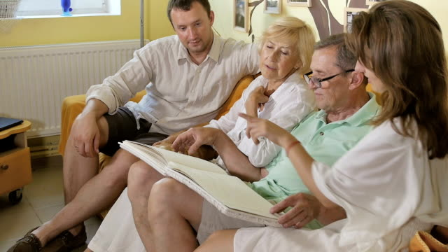 Family sits on a sofa and consider the book. video