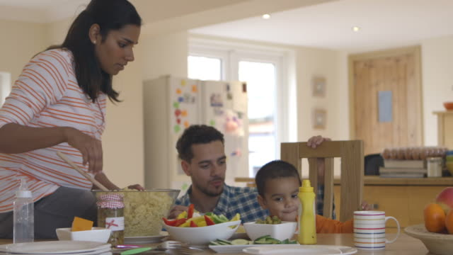 Family Sitting At Table In Kitchen Eating Meal With Son video