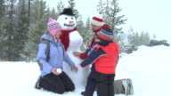 Family sitting by snowman video