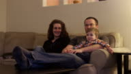 A family sitting down on the couch to watch television together video