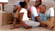 Family sitting in new home video