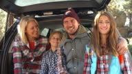 Family sitting in open trunk of car, close up handheld shot video