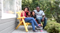 Family sitting on bench on porch smiling video