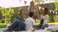 Family Sitting On Blanket In Garden Blowing Bubbles video