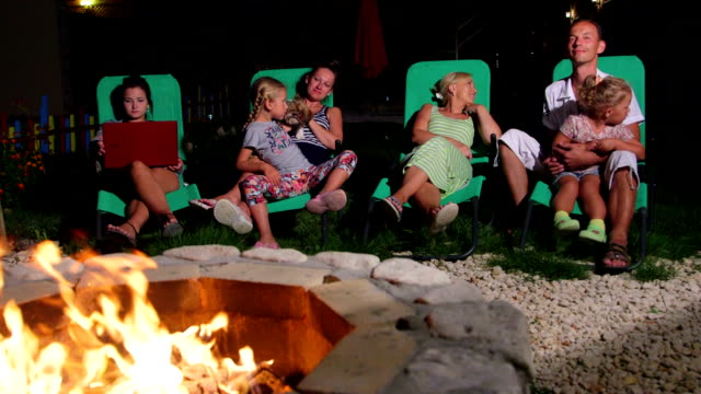 Family sitting on patio loungers in backyard near flaming fire pit at twilight video