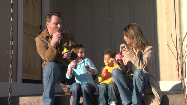 Family sitting on porch blowing bubbles video