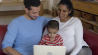 Family Sitting On Sofa And Looking At Laptop Together video