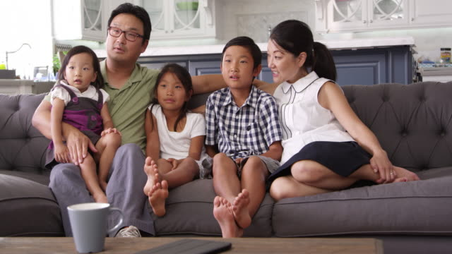 Family Sitting On Sofa At Home Watching TV Shot On R3D video