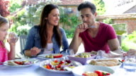 Family Sitting Outdoors Around Table Eating video