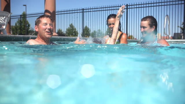 Family splashing and playing in pool video