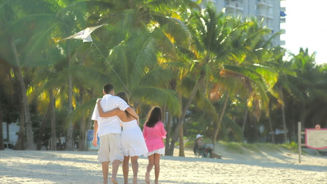 Family stroll along beach together video