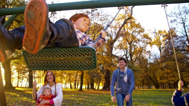 SLO MO Family swinging in the park video