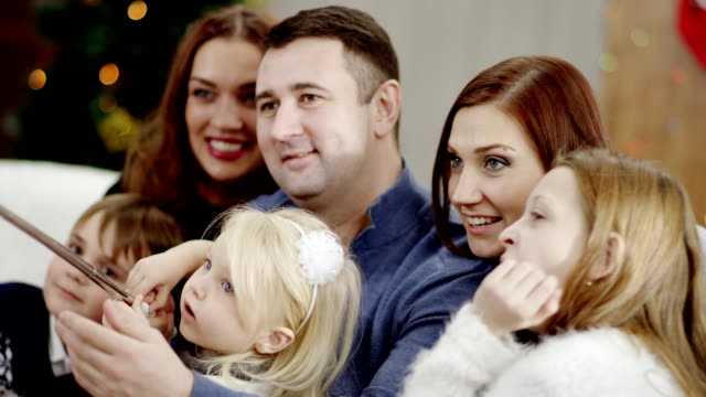 family taking photo with selfie stick at christmas party video