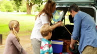 Family unloading their car for a camping trip video