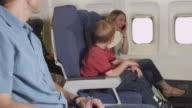 Family using cellphone on plane video