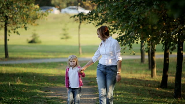 Family values: Mother and child walking in autumn park video