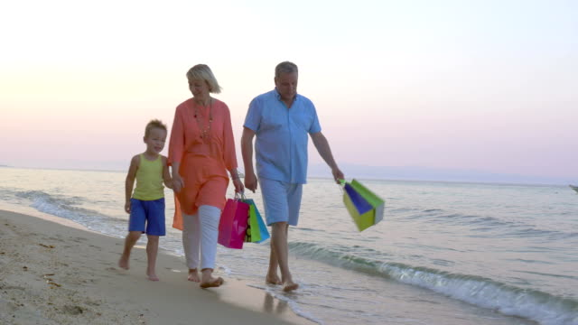 Family walk on the beach after shopping video
