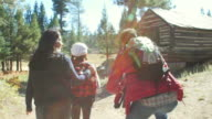 Family walk past cabin in a forest, dad puts son on shoulder, shot on R3D video