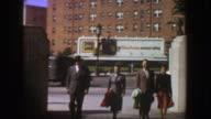 1957: Family walking 50s style advertisement billboard background. video