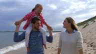 Family walking along sea shore with father carrying daughter on shoulders video