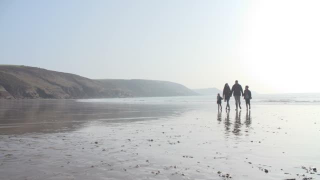 Family Walking Along Winter Beach In Slow Motion video