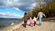 Family walking on sandy bank of river video