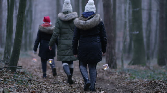 R/F Family walking through a forest with lanterns video