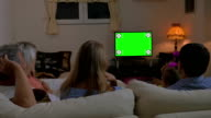 Family watching TV at home, chroma key video