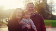 Family with a little boy posing for a photo, in golden light with lens flare video