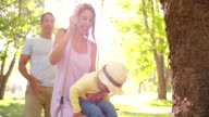 Family with a little girl swinging happily in the park video