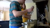 family with baby prepare dinner in kitchen. Mom taste soup spoon video