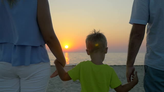 Family with child looking at sunset over sea video