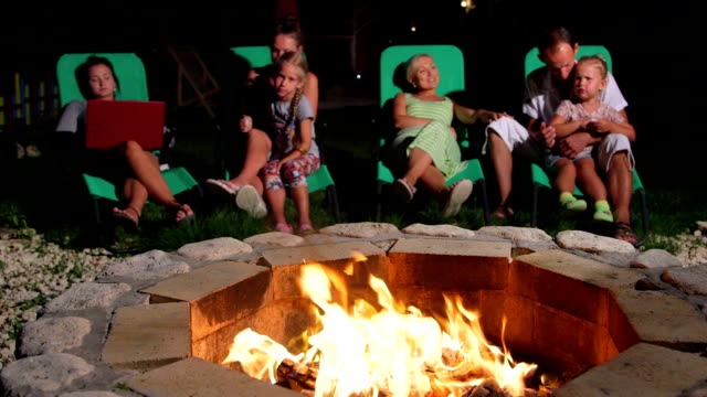 Family with children and friends relaxing near stone patio fire pit outdoor video