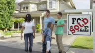 Family with 'For Sale, Sold' real estate sign video