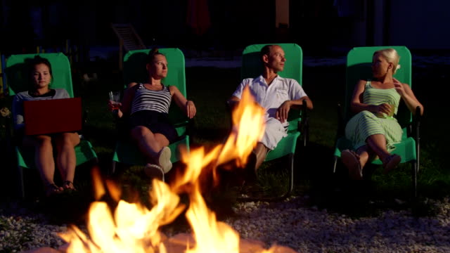 Family with friends relaxing on grass lawn in backyard near stone fire pit video