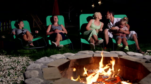 Family with friends relaxing on grassy lawn in backyard of home near fire pit video