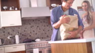 Family with Infant Daughter Unpacking Groceries in Kitchen video