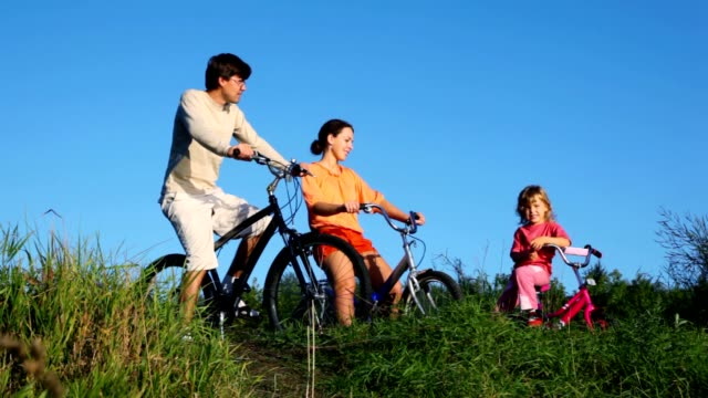 family with little daughter sits on bicycles and talks video