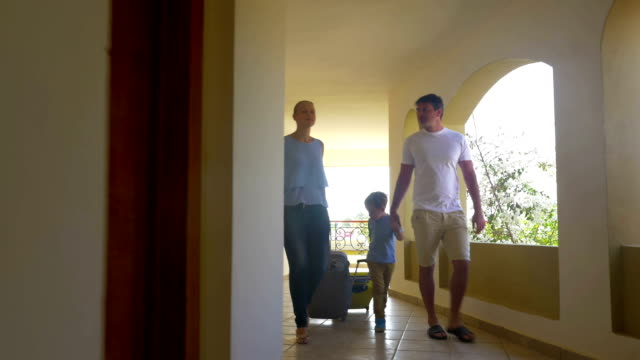 Family with rolling bags in hotel corridor video