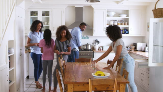 Family With Teenage Children Laying Table For Meal In Kitchen video